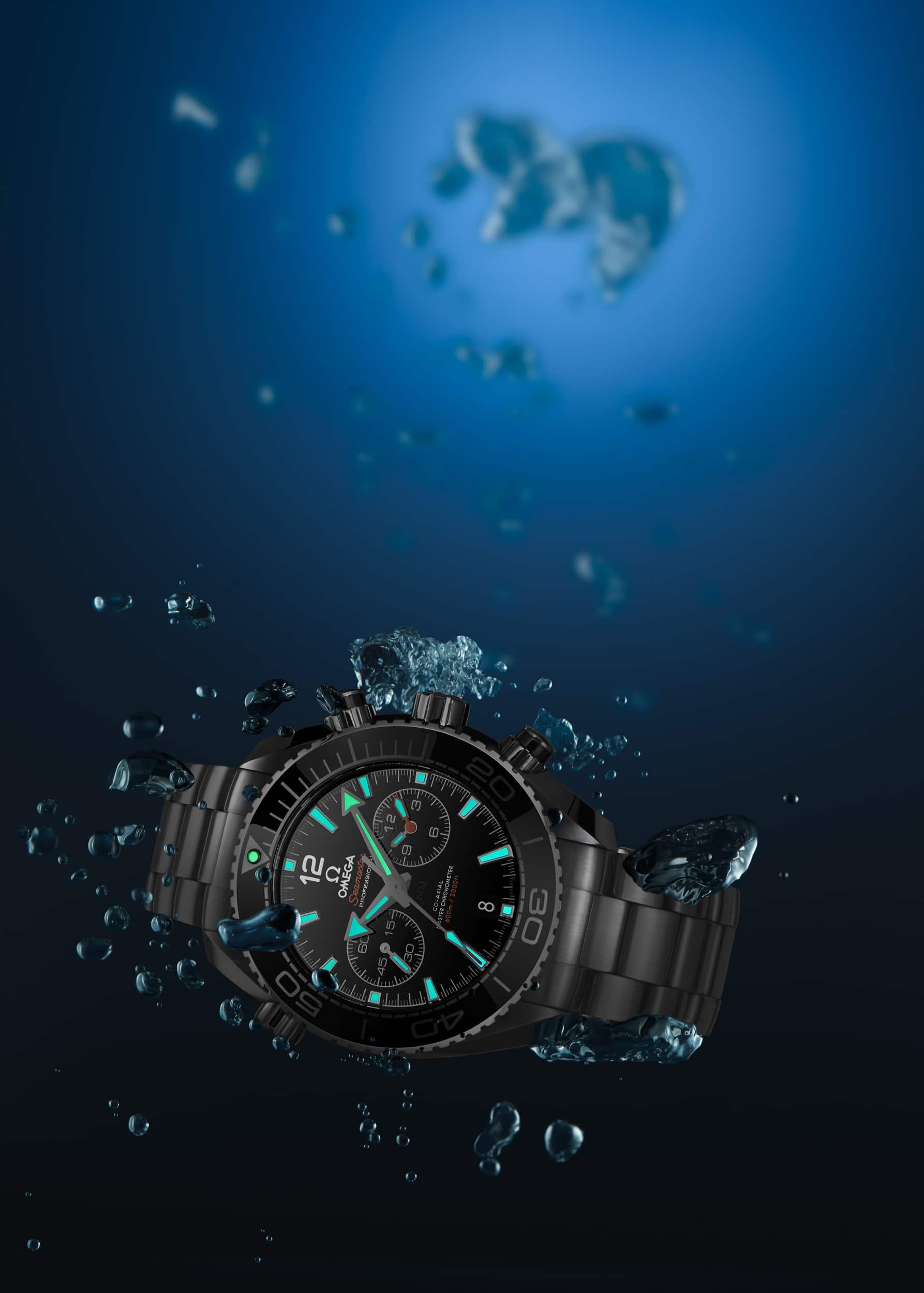 Werbeaufnahme einer Omega Planet Ocean Chronograph 600m Taucheruhr in der Tiefe unter Wasser mit leuchtender Superluminova | Fotograf in der Region Osnabrück Münster Bielefeld für Werbefotografie