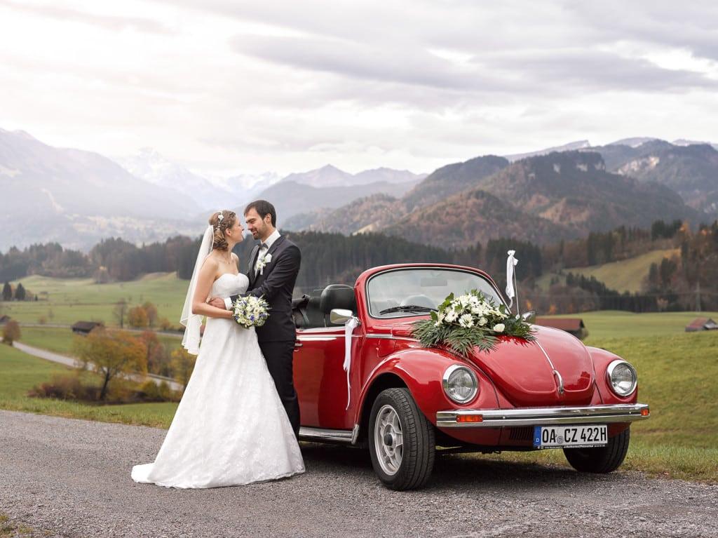 Brautpaar mit VW Käfer Oldtimer vor auf einem Hügel mit den Alpen im Hintergrund | Hochzeitsfotograf im Allgäu
