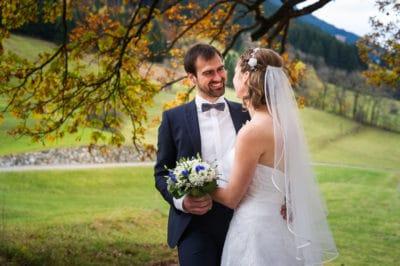 Hochzeitsfoto eines Brautpaars unter einem herbstlichen Baum