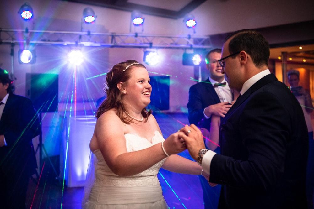 Brautpaar bei der Hochzeitsparty auf der Tanzfläche mit buntem Licht und Nebel