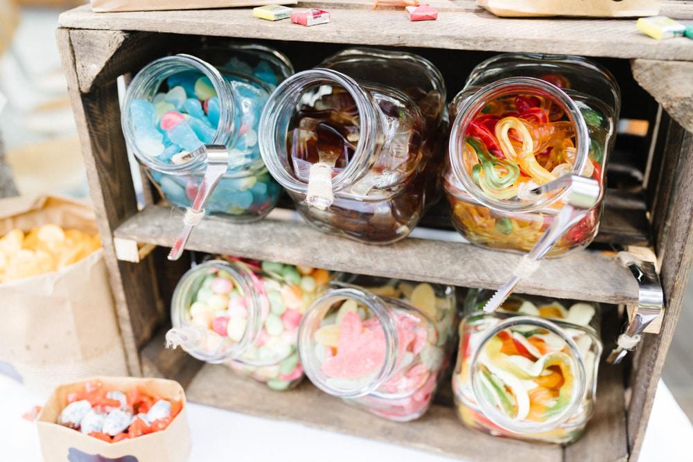 Eine Candybar auf einer Hochzeit mit hübsch angerichteten Fruchtgummi, Schokolade und Chips