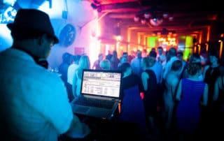 DJ mit Laptop und tanzenden Hochzeitsgästen im Hintergrund