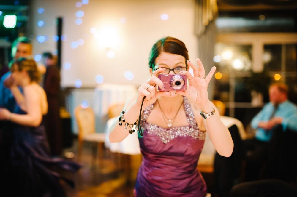Freundin der Braut macht Fotos mit einer kleinen Kamera, deren Farbe wunderbar zu ihrem weinroten Kleid passt