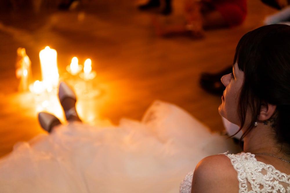 Braut im Kerzenlicht zum Ende der Hochzeitsparty hin