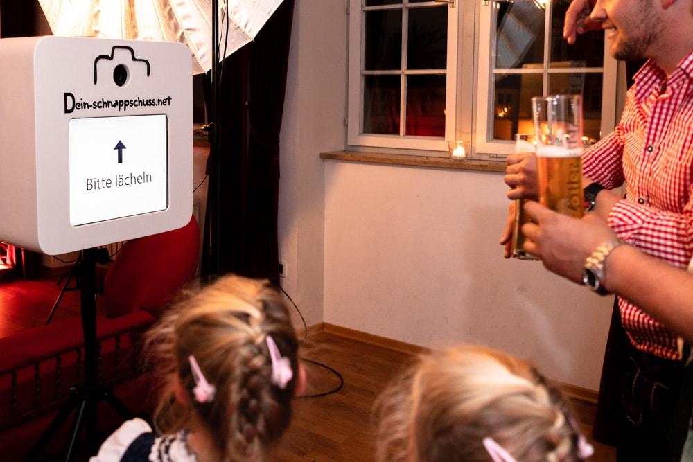 Erwachsene Gäste und Kinder fotografieren sich selbst in einer Photo Booth