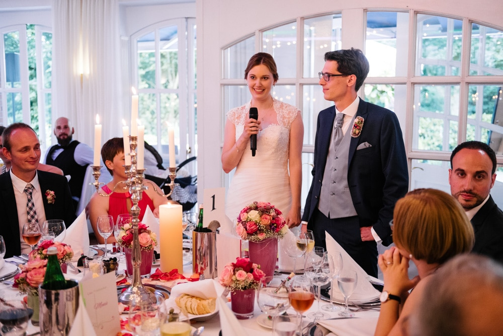 Brautpaar hält eine kleine Rede am Tisch vor der Party
