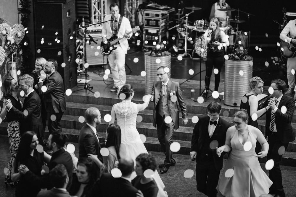 Brautpaar tanzt inmitten der Gäste auf großer Tanzfläche mit Liveband