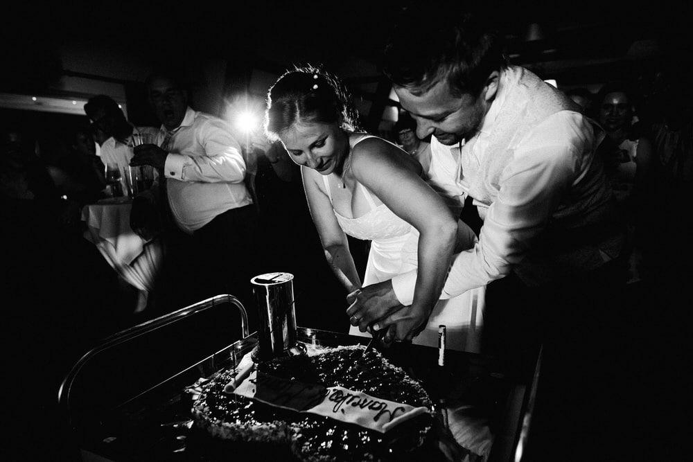 Brautpaar beim Anschneiden der Hochzeitstorte auf der Tanzfläche